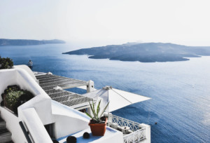 Looking over the coast of Santorini behind white buildings